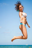 Den härliga kvinnan hoppar mot blå himmel Arkivbilder