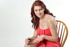 Den härliga kvinnan i badlakanet som sätter på, spikar polermedel Arkivfoton