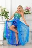 Den härliga kvinnan i blått klär i lyxig inre. arkivbild