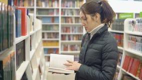 Den härliga kvinnan i en bokhandel granskar en bok arkivfilmer