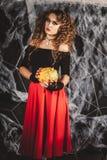 Den härliga kvinnan i en dräkt för häxa` s är hållande pumpa som är främst av den svarta väggen med den netto spindeln Royaltyfria Bilder