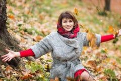 Den härliga kvinnan i en färgrik höstskog sitter på jordningen arkivfoton