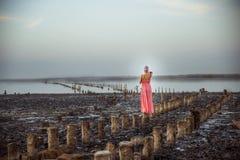 Den härliga kvinnan i en korallklänning blir på saltar kolonnen fotografering för bildbyråer