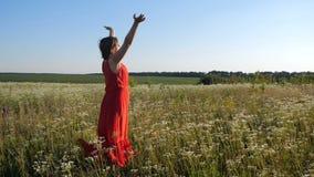 Den härliga kvinnan i en röd klänning gör en andasövning i ett fält i slo-mo stock video