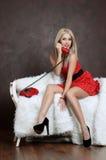 Den härliga kvinnan i en röd klänning med den gamla telefonen Arkivfoto