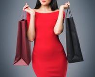 Den härliga kvinnan i en röd klänning rymmer utsmyckade shoppingpåsar Grå färgbakgrund Arkivbilder
