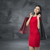 Den härliga kvinnan i en röd klänning rymmer utsmyckade shoppingpåsar Samtida bakgrund royaltyfri fotografi