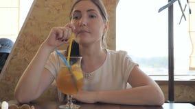 Den härliga kvinnan i ett kafé dricker en coctaildrink arkivfilmer