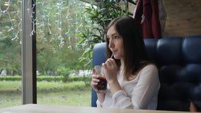 Den härliga kvinnan i ett kafé rör funderat vin stock video