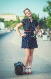 Den härliga kvinnan i femtiotal utformar med hänglsen som rymmer retro camer fotografering för bildbyråer
