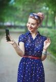Den härliga kvinnan i femtiotal utformar med hänglsen som tar bilden av H arkivfoton