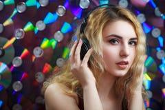 Den härliga kvinnan i hörlurar har gyckel och lyssnar musik Royaltyfri Bild
