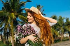 Den härliga kvinnan i hatt med blommor känner sig fritt Royaltyfria Foton