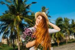Den härliga kvinnan i hatt med blommor känner sig fritt Arkivfoto