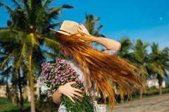 Den härliga kvinnan i hatt med blommor känner sig fritt Royaltyfri Bild