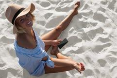 Den härliga kvinnan i hatt- och klänningsammanträde på sand sätter på land royaltyfria bilder