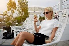 Den härliga kvinnan i iklädd trendig dyr kläder för solglasögon är det läs- textmeddelandet på mobiltelefonen, arkivbilder