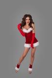 Den härliga kvinnan i jul klär att posera mot oavkortad höjd för grå bakgrund arkivbild