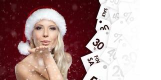 Den härliga kvinnan i jullockslag kysser för de som söker efter ett bra pris royaltyfri bild