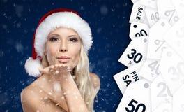 Den härliga kvinnan i jullockslag kysser till alla köpare Arkivbild