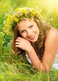 Den härliga kvinnan i krans av blommor ligger i det gröna gräset ut Royaltyfri Bild