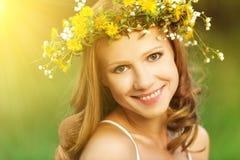 Den härliga kvinnan i krans av blommor ligger i det gröna gräset ut Arkivfoto