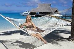 Den härliga kvinnan i långa sundress i en hängmatta på en havsbakgrund Royaltyfri Foto
