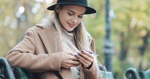 Den härliga kvinnan i laget som använder smartphonen, kopplar av på bänken i höst parkerar Teknologi utomhus royaltyfri bild