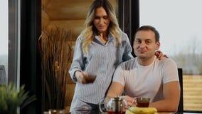Den härliga kvinnan i pyjamas häller hennes makete och att krama honom i kök- och drinkteet Vänner lager videofilmer
