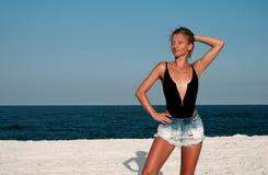 Den härliga kvinnan i svart baddräkt och jeans kortsluter på stranden Arkivfoto
