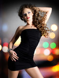 Den härliga kvinnan i svart klänning poserar över nattljus arkivfoton