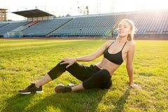 Den härliga kvinnan i svart sportswear vilar efter en tung genomkörare på det gröna gräset av stadion arkivfoto