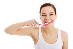 Den härliga kvinnan i vitöverkant borstar hennes tänder. Arkivfoton