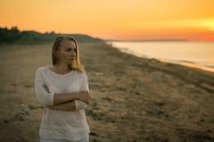 Den härliga kvinnan i vit beklär att tycka om solnedgången på stranden Royaltyfria Foton