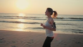 Den härliga kvinnan joggar på havskust på solnedgången som kör på stranden med telefonen arkivfilmer