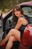Den härliga kvinnan kastar en blick ut ur den röda bilen Arkivbilder