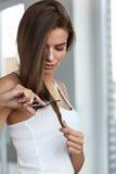 Den härliga kvinnan klipper kluvna hårtoppar av långt hår med sax Royaltyfri Bild