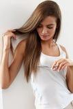 Den härliga kvinnan klipper kluvna hårtoppar av långt hår med sax Arkivbild