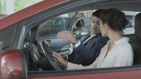 Den härliga kvinnan kontrollerar kabinen för bil` s i bilvisningslokal med representanten stock video