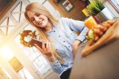 Den härliga kvinnan kontrollerar nyheterna på sociala nätverk i ett hemtrevligt julkafé i stilen av Provence Arkivfoton