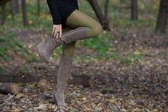 Den härliga kvinnan lägger benen på ryggen i mockaskinnkängor i höstskog Arkivbild