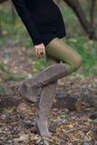 Den härliga kvinnan lägger benen på ryggen i mockaskinnkängor i höstskog Arkivfoto