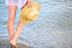 Den härliga kvinnan lägger benen på ryggen på stranden i havsvatten royaltyfria bilder