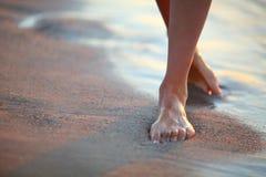 Den härliga kvinnan lägger benen på ryggen på stranden på soluppgång royaltyfria bilder