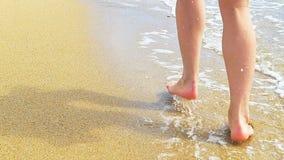 Den härliga kvinnan lägger benen på ryggen, runn längs sandstranden gå vatten stock video
