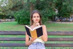 Den härliga kvinnan läser en bok, och tänka om något på bänken i parkera Flickan har några tankar och idéer royaltyfri bild