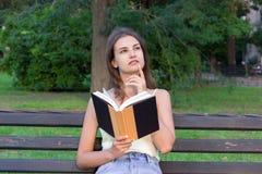 Den härliga kvinnan läser en bok, och tänka om något på bänken i parkera Flickan har några tankar och idéer royaltyfri foto