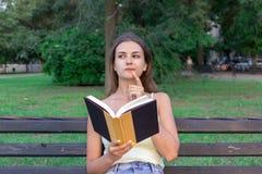 Den härliga kvinnan läser en bok, och tänka om något på bänken i parkera Flickan har några tankar och idéer royaltyfria foton