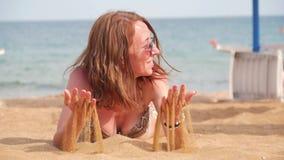 Den härliga kvinnan ligger på stranden och den hällande sanden från henne händer Lycklig kvinna för strand som solbadar att ligga lager videofilmer