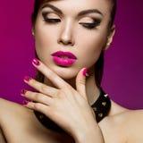 Den härliga kvinnan med aftonsmink och rosa färger spikar taggar Arkivfoto